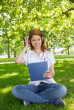 Pretty redhead using her tablet pc while listening to music in the park Stock Images