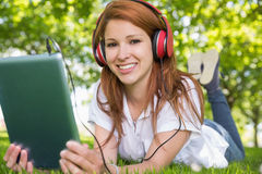 Pretty redhead using her tablet pc while listening to music in the park Royalty Free Stock Photos