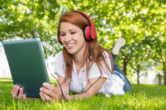 Pretty redhead using her tablet pc while listening to music in the park Stock Photography