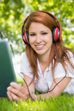 Pretty redhead using her tablet pc while listening to music in the park Royalty Free Stock Photography