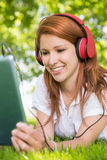 Pretty redhead using her tablet pc while listening to music in the park Royalty Free Stock Photo