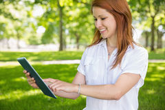 Pretty redhead using her tablet pc in the park Stock Photo