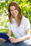 Pretty redhead using her tablet pc in the park Royalty Free Stock Photography
