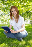 Pretty redhead using her tablet pc in the park Royalty Free Stock Images