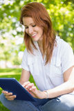 Pretty redhead using her tablet pc in the park Royalty Free Stock Photos
