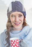 Pretty redhead in warm clothing holding mug Stock Images