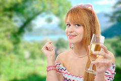 Pretty redhead woman drinks a glass of wine, greenery on backgr Stock Images