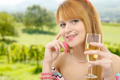 Pretty redhead woman drinks a glass of wine, vineyards backgrou Royalty Free Stock Photo