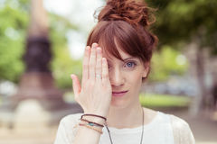 Pretty redhead woman holding her hand to her eye Royalty Free Stock Photos