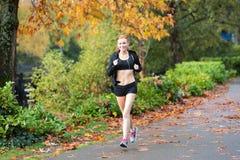 Pretty redhead woman jogging outside Royalty Free Stock Image