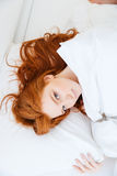 Pretty redhead woman with long hair lying in bed Royalty Free Stock Photo