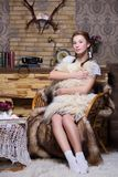 Pretty redhead woman. With pigtails sitting on the chair near a fireplace stock photography