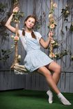 Pretty redhead woman. In short flowery dress sitting on a swing royalty free stock photo