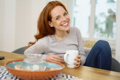 Pretty redhead woman relaxing with a cup of coffee. At home with her feet up on the sofa stock photo