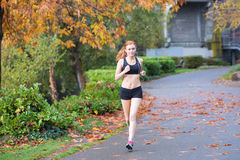 Pretty redhead woman running outside Royalty Free Stock Photos