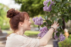 Pretty redhead woman smelling the lilac stock images