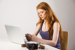 Pretty redhead working on laptop and camera Stock Images