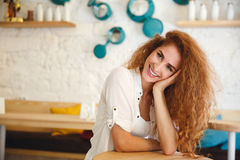 Pretty redhead young lady sitting in cafe while posing. Stock Photography