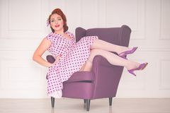 Pretty redheaded pin up woman wearing pink polka dot dress and posing with purple armchair on white background. Alone royalty free stock image