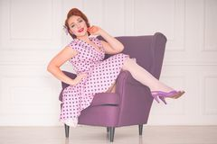 Pretty redheaded pin up woman wearing pink polka dot dress and posing with purple armchair on white background. Alone stock photo