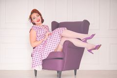 Pretty redheaded pin up woman wearing pink polka dot dress and posing with purple armchair on white background. Alone royalty free stock photo