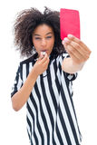 Pretty referee blowing her whistle and showing red card. On white background Stock Photos