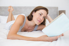 Pretty relaxed woman reading book in bed Royalty Free Stock Photos