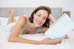 Pretty relaxed woman reading book in bed Stock Photography