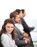 Pretty representative at her desk with colleagues Royalty Free Stock Photos