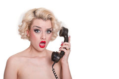 Shocked blond beauty on vintage telephone. Pretty retro blond on vintage telephone looking shocked - isolated on white Royalty Free Stock Images