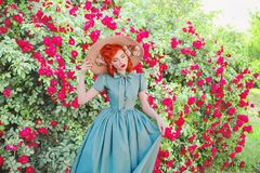 Pretty retro girl with red lips in mint dress on a beautiful summer background.  Fashionable summer clothes. Young luxury redhead Stock Photos