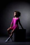 Pretty rhythmic gymnast sitting on cube in studio Royalty Free Stock Photo