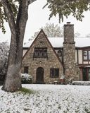 Pretty rock house with arched door and Tudor style leaded glass diamond panel windows during snowfall stock images