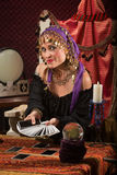 Pretty Roma Fortune Teller. Beautiful Roma woman with crystal ball and tarot cards Royalty Free Stock Photography
