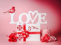 Pretty romantic composition for Valentines day. Love you message with gift box, red ribbons and decoration. Festive greeting. Concept. Love declaration concept stock photos