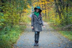Pretty romantic girl in autumn clothes walks in a park. The mood of autumn, leaf fall. Stock Photo