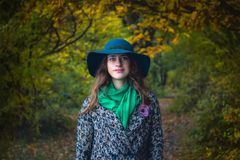 Pretty romantic girl in autumn clothes walks in a park. The mood of autumn, leaf fall. Royalty Free Stock Image