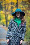 Pretty romantic girl in autumn clothes walks in a park. The mood of autumn, leaf fall. Royalty Free Stock Photo