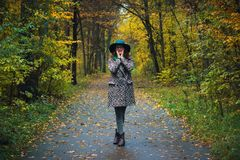 Pretty romantic girl in clothes walks in a park. The mood of autumn, leaf fall. Autumn fashion. Stock Photos