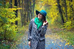 Pretty romantic girl in clothes walks in a park. The mood of autumn, leaf fall. Autumn fashion. Stock Images