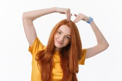 Pretty romantic young redhead woman making a heart gesture with a happy tender smile.  stock image