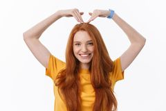 Pretty romantic young redhead woman making a heart gesture with a happy tender smile.  royalty free stock photos