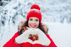 Pretty romantic young woman making a heart gesture with her fingers in front of her chest showing her love on winter royalty free stock images