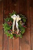 Pretty,rustic holiday wreath on barn board. Royalty Free Stock Photo