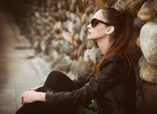 Pretty sad girl sits on street. Royalty Free Stock Photos