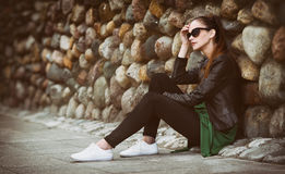 Pretty sad girl sits on street. Royalty Free Stock Photography
