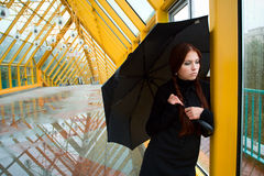 Pretty sad girl by the window. Pretty sad girl with umbrella by the window Stock Image