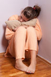 Pretty sad teenage girl curled up in the corner Royalty Free Stock Image