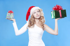 Pretty Santa girl hiding a present gifts for New Y Royalty Free Stock Photos