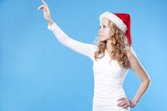 Pretty Santa girl pointing on empty space Royalty Free Stock Image
